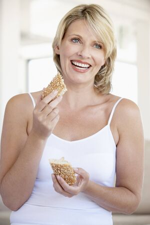 Mid Adult Woman Eating Fresh Brown Bread Roll Stock Photo - 4546815