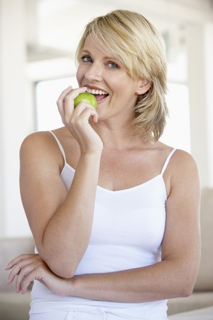 woman eat: Mid Adult Woman Eating Green Apple