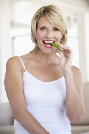 celery: Mid Adult Woman Smiling At Camera And Eating Celery Stick Stock Photo