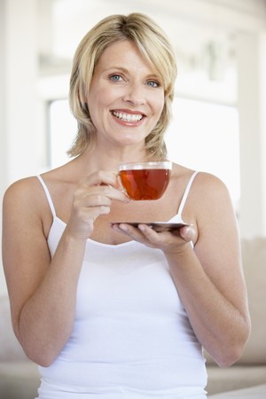 Mid Adult Woman Holding Tea Cup And Smiling At Camera photo