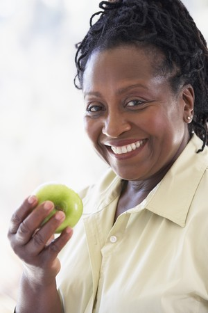 older person: Senior Woman Eating Green Apple And Smiling At The Camera Stock Photo