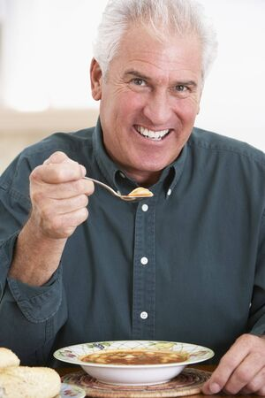 hombre comiendo: Senior Man sopa, sonriente en la c�mara de alimentaci�n Foto de archivo