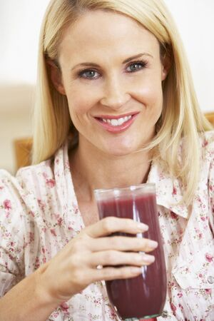 Mid Adult Woman Holding A Fresh Berry Smoothie photo
