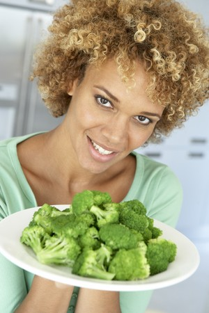 Mid Adult Woman Holding A Plate Of Broccoli, Smiling At The Camera photo