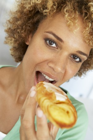 Mid Adult Woman Eating A Pastry photo