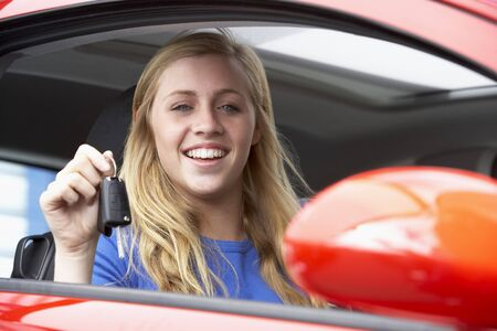 Teenage Girl Sitting In Car, Holding Car Keys And Smiling At The Camera photo