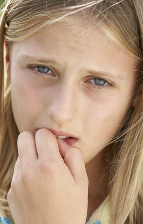preteen girl: Portrait Of Girl Biting Nails Stock Photo