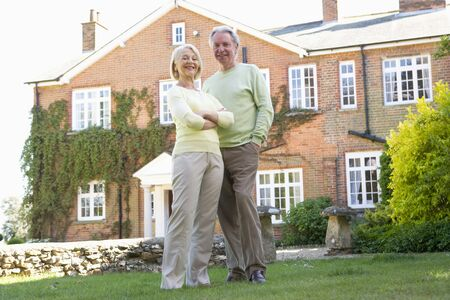 wealthy: Couple Standing Outside Their House Stock Photo