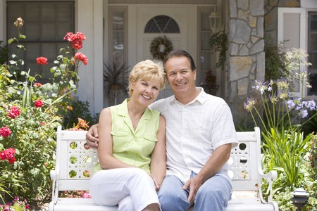 Couple Sitting On Bench Outside House photo