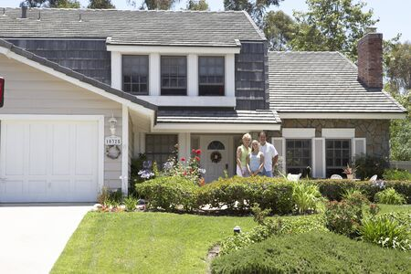 Family Standing Outside House photo