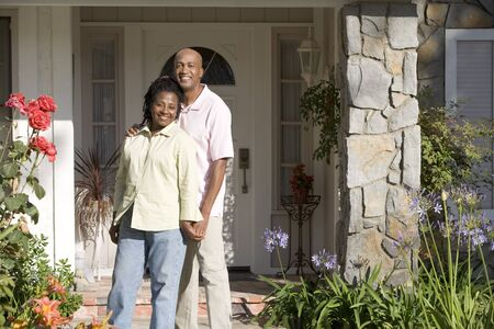 in front of the house: Couple Standing Outside Their House Stock Photo