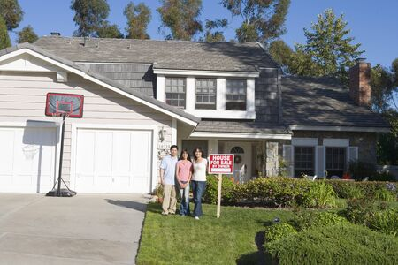 Family Standing Outside House With Real Estate Sign photo