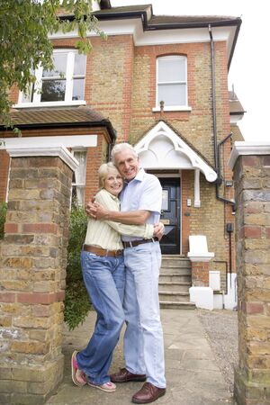 outside of house: Couple Standing Outside Their House Stock Photo