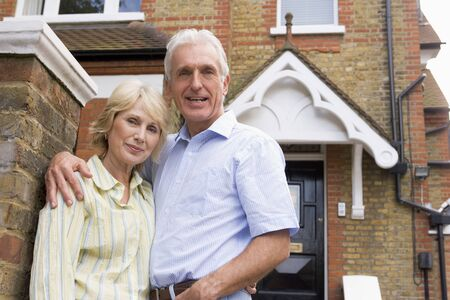 home ownership: Couple Standing Outside Their House Stock Photo