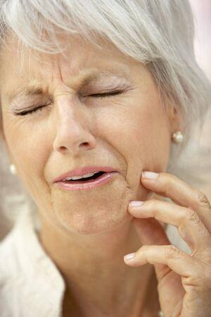 Senior vrouw met een Kiespijn Stockfoto