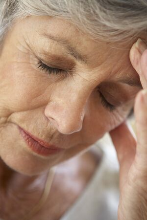 weary: Senior Woman With Head In Hands Looking Weary
