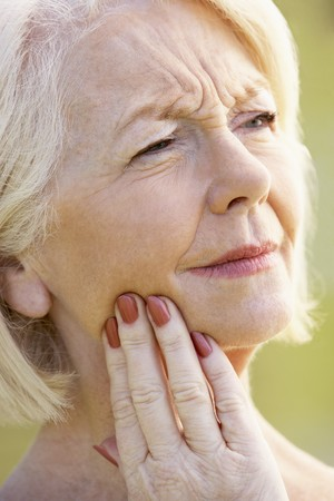 Portrait Of Senior Woman With A Toothache photo