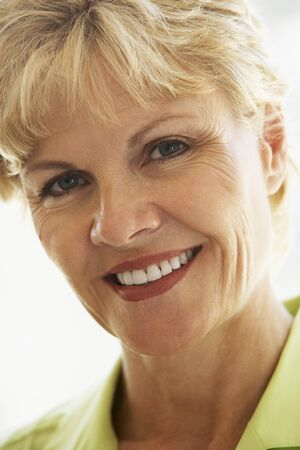 middle aged woman smiling: Portrait Of Middle Aged Woman Smiling At Camera