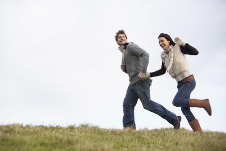 Couple Holding Hands And Running In The Park photo