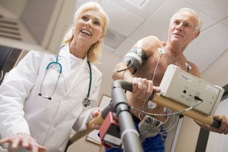 Doctor Monitoring The Heart-Rate Of Patient On A Treadmill photo