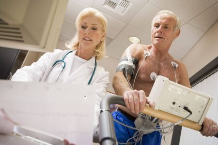 heartrate: Doctor Monitoring The Heart-Rate Of Patient On A Treadmill Stock Photo