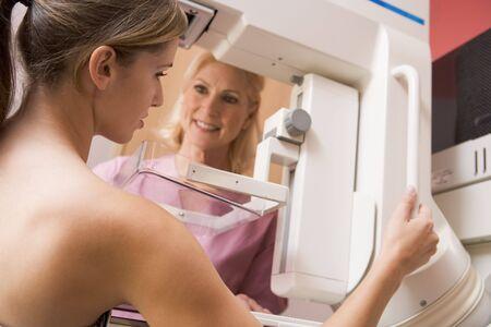 screening: Nurse Assisting Patient Undergoing Mammogram