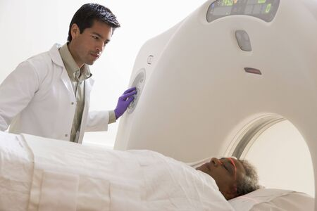 Doctor With Patient Having A Computerized Axial Tomography (CAT) Scan photo