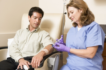 oncology: Nurse Giving Patient Injection Through Tube Stock Photo