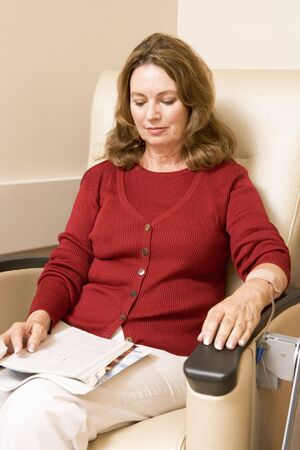chemo: Patient Reading Magazine While Being Monitored Stock Photo