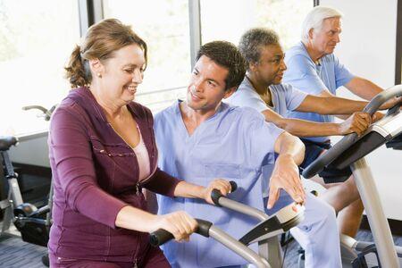 fisioterapia: La enfermera con el paciente en rehabilitaci�n con ejercicios de m�quina