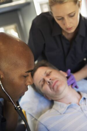 Paramedic using stethoscope on patient in ambulance photo