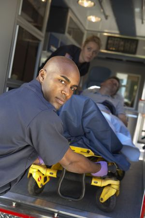 Paramedics preparing to unload patient on gurney photo