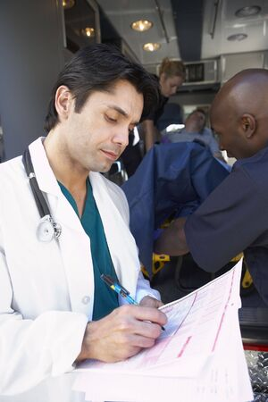 Doctor taking notes as paramedics unload patient photo