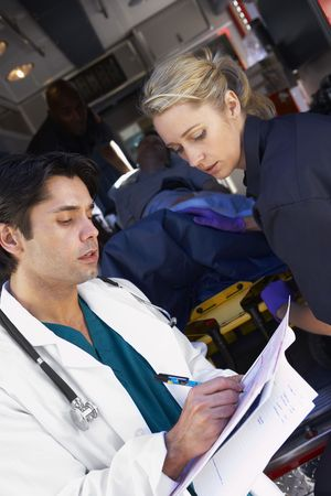 Paramedic advising doctor about arriving patient photo