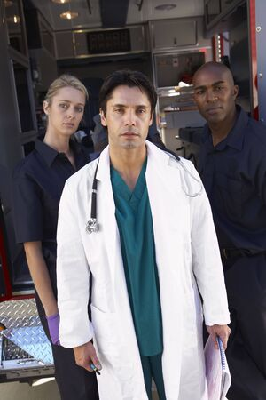 Portrait of doctor with two paramedics in front of ambulance photo