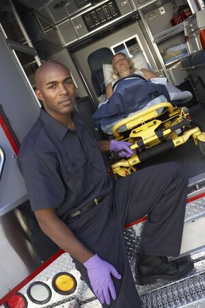 Male paramedic preparing to unload patient from ambulance photo