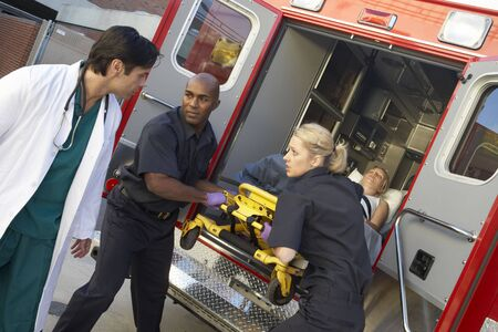 Paramedics and doctor unloading patient from ambulance photo