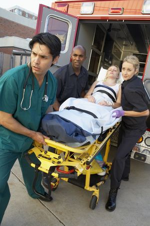 Paramedici en arts lossen patiënt uit ambulance