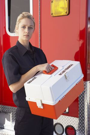Paramedic standing by ambulance with medical kit photo