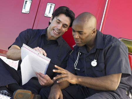 cheerfully: Two paramedics cheerfully doing paperwork, sitting by their ambulance