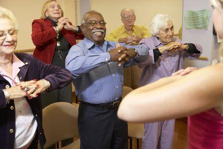 terapia grupal: Adultos mayores en una clase de estiramiento