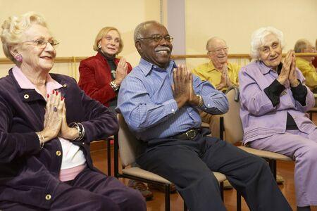 men exercising: Adultos mayores en una clase de estiramiento