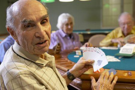 Senior adults playing bridge photo