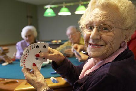 happy old people: Senior adults playing bridge Stock Photo
