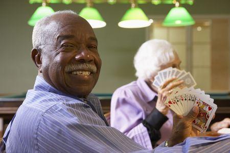 80s adult: Senior hombre jugando al bridge Editorial