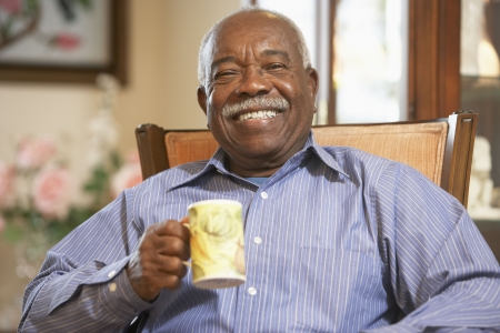 Senior man drinking hot beverage photo