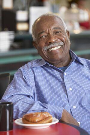 one senior adult man: Senior man having morning tea
