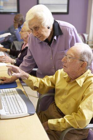 Senior woman helping senior man use computer photo