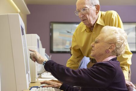 silver surfer: Senior man helping senior woman to use computer