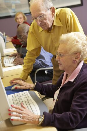 Senior man helping senior woman to use computer photo